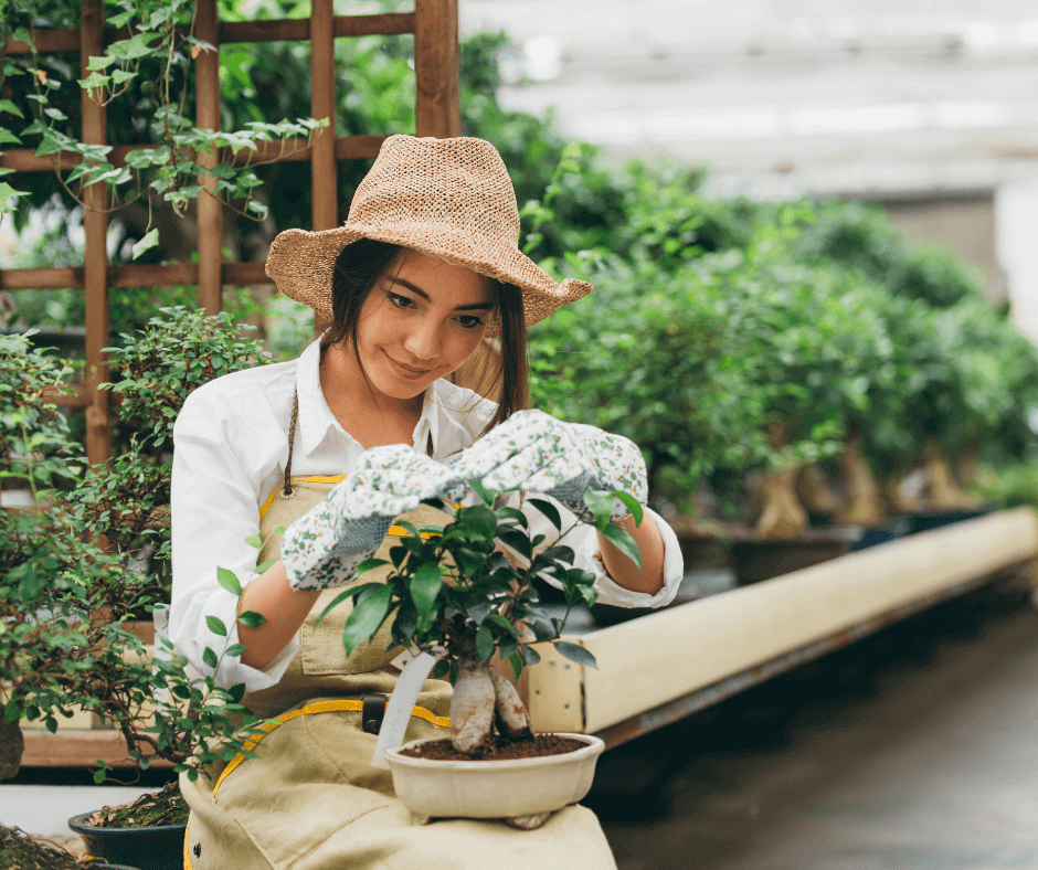Woman tending to her plants in the greenhouse