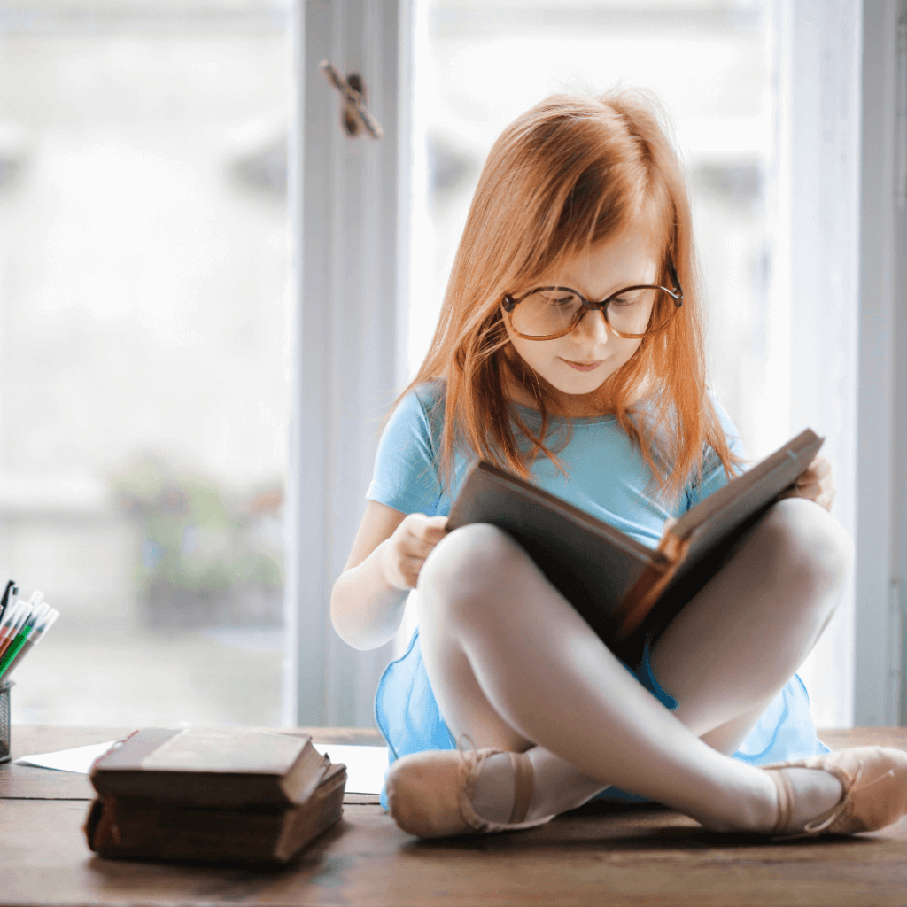 Young girl reading a book next to the window