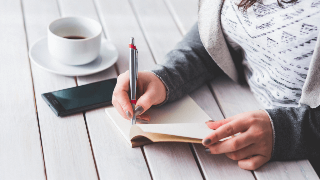 Woman sat a table writing in her diary