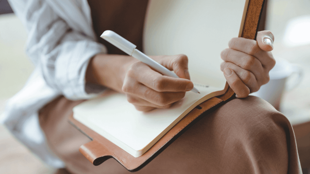 Woman writing ideas in a journal