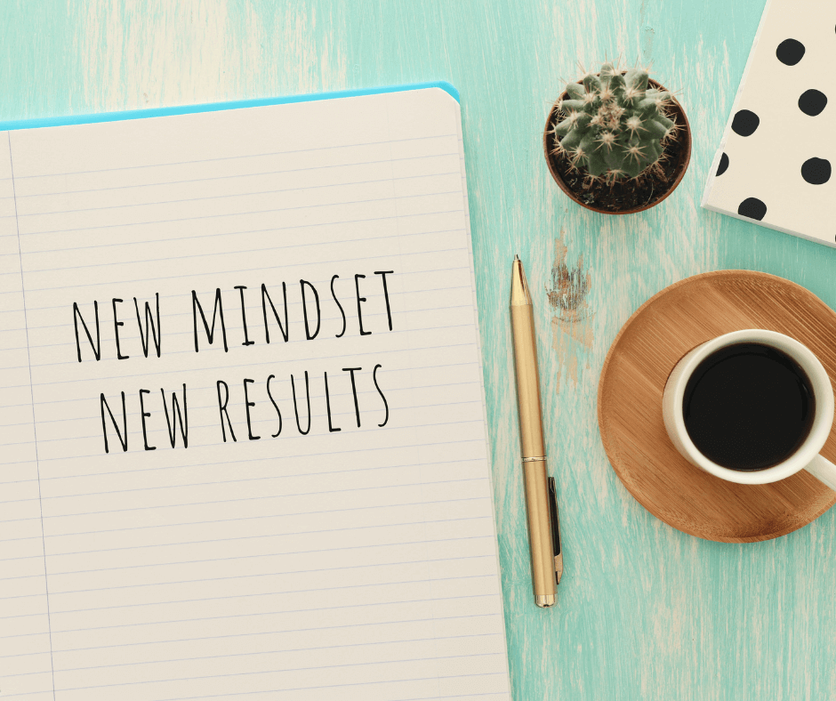 """Notebook on a table with """"New Mindset New results"""" written on it"""