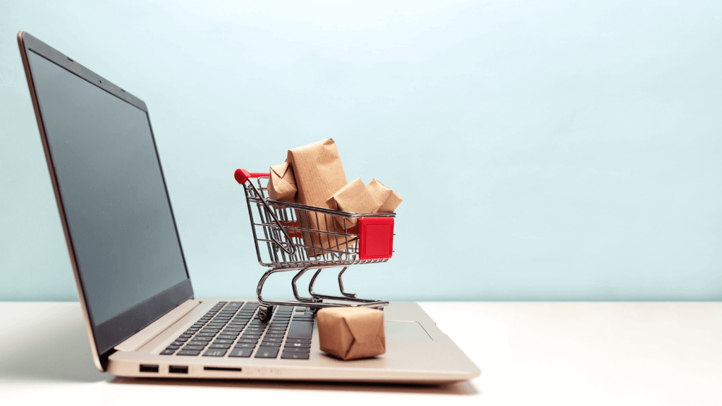 A miniature sized shopping trolley full of parcels on a laptop